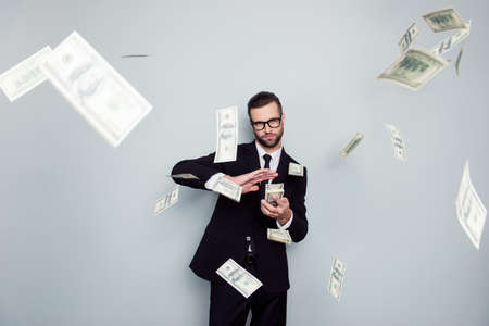 Spectacles jackpot entrepreneur economist banker chic posh manager jacket concept. Handsome confident cunning clever wealthy rich luxury guy holding wasting stack of money isolated on gray background Foto de archivo