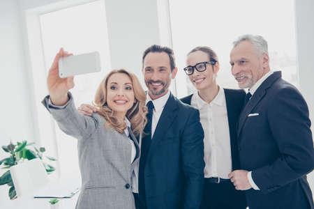 Portret van aantrekkelijke, vrolijke, stijlvolle, zelfverzekerde zakelijke personen staan op de werkplek, station, fotograferen selfie op camera aan de voorkant, met behulp van slimme telefoon, pauze, pauze, time-out