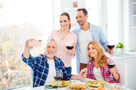 Cheerful, joyful relatives, stylish company, festive couples having fun in house, room, apartment, handsome senior with grey hair shooting self portrait on smart phone, family photo