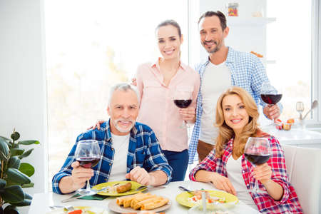 Portrait of beautiful girlfriends, cheerful relatives, attractive, handsome boyfriends having fun in house, room, apartment, drinking wine, eating meals, looking at camera, family photo