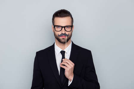 Portrait of confident attractive handsome executive concentrated hypocrite creative smart intelligent cunning tricky employer with false black mustache isolated on gray background