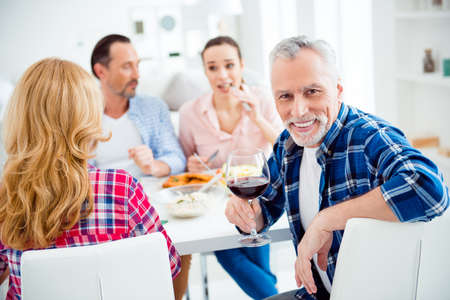 Attractive, stylish senior with grey hair, stubble turning, looking at camera holding glass of red wine, alcohol while sitting at the table in house, apartment, room with guests, visitors, relatives Stock Photo