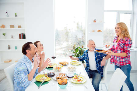 Cheerful, beautiful, attractive, stylish, mature woman carries a plate with chops, she cooked a lot of dishes for guests, visitors, festive company sitting in house, room, apartment, drinking, eating Stock Photo