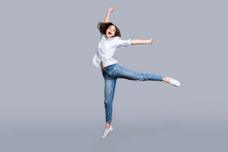 Full length, full size, fullbody portrait of pretty, charming, modern, stylish girl jumping in the air yelling with wide open mouth, celebrating successfully pass exams, isolated on grey background Banco de Imagens - 98979281