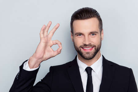 Close up portrait of cheerful excited handsome attractive friendly kind delightful with modern stylish fashionable hairstyle demonstrating ok symbol isolated on gray background