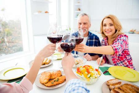 スタイリッシュで魅力的な陽気なシニアカップルの肖像画は、家の中で子供たちと食事を楽しんで、赤ワイン、アルコール、テーブルの上に食欲を