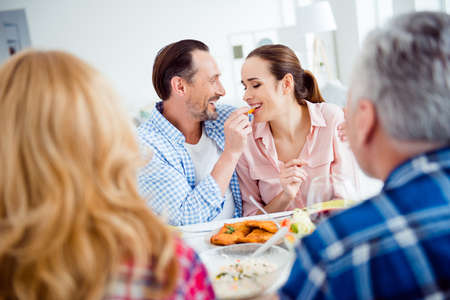 Portrait of attractive, cute, sweet, lovely, festive, cheerful couple sitting with friends in house, apartment, room, visiting parents, men feeding his woman, giving food with fingers, having fun Stock Photo