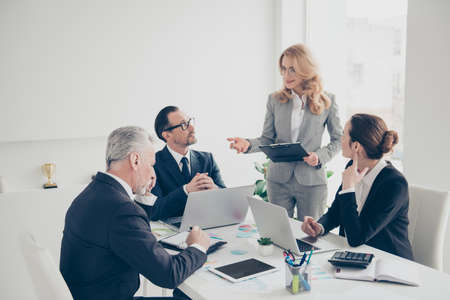 Beautiful, attractive, stylish, blonde woman in suit standing, speaking, talking during conversation, concentrated business persons sitting in work place, station, listening, making notes