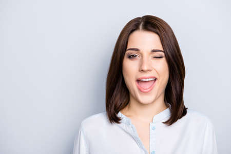 Close up portrait of nice, modern, trendy woman having short hair and open mouth, blinking with eye, isolated on grey background