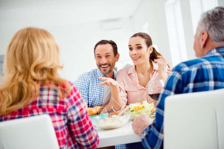 Stylish, cheerful, attractive couple having dinner with relatives, boyfriend hugging, embracing his girlfriend, sitting in house, apartment, room, girl telling to her mother gesturing with hand Stock Photo