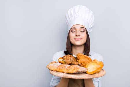 Seller customer palatable gourmet service industry people professional rack concept. Close up portrait of delightful  peaceful lady smelling appetizing freshly baked products isolated gray background
