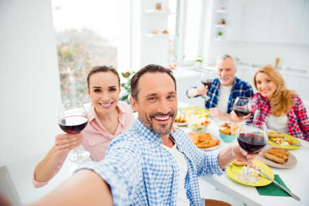 Bearded, handsome, attractive, cheerful, stylish men shooting self portrait with his relatives, guests, visitors,  gathering in house, apartment, room, sitting at the table, eating food, drinking wine