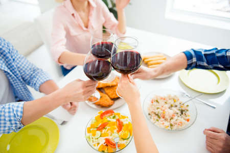 Cropped portrait of people's hands clinking glasses of red wine sitting at the table with appetizing dishes, having dinner, supper together, drinking, sharing alcohol Standard-Bild - 98979843