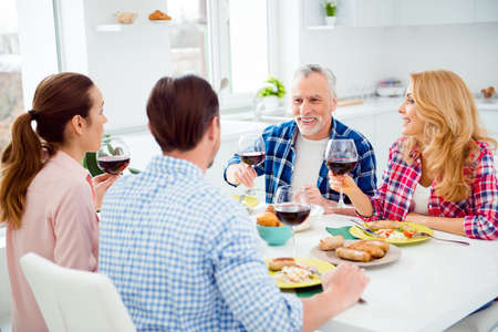 Handsome, attractive, middle-aged man with grey hair saying toast holding glass of alcohol, congratulating guests, visitors, festive company sitting in house, apartment, room, eating, drinking