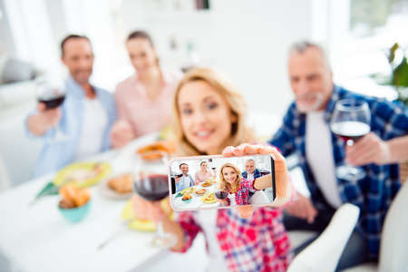 Portrait with empty place, copy space of smiling, cheerful couples meet, gather in house, room, apartment, beautiful woman making photo, showing black touch screen of smart phone to the camera