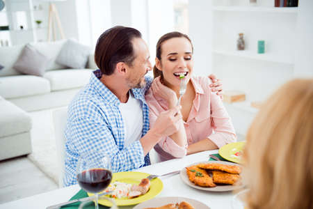 Portrait of attractive, cute, sweet, lovely, festive, cheerful couple sitting with friends in house, apartment, room, visiting parents, men feeding his woman, giving food with fork, having fun Stock Photo