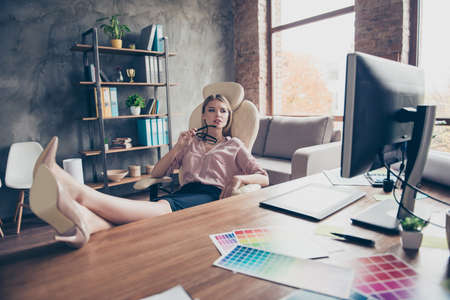 Pretty, attractive ponder minded woman, sitting on chair in open space workplace, putting legs on the table, watching, looking at monitor screen, holding spectacles in hand Imagens