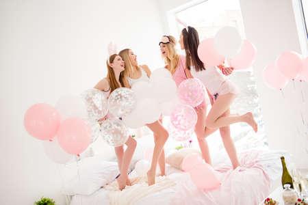 Porträt von hübschen, netten, bezaubernden, dünnen, attraktiven, coolen, lustigen Mädchen in kurzen Hosen, die Innen chillen, das Treffen genießen und einander betrachten und die Kleiderordnung haben und auf Bett stehen Standard-Bild - 99473405