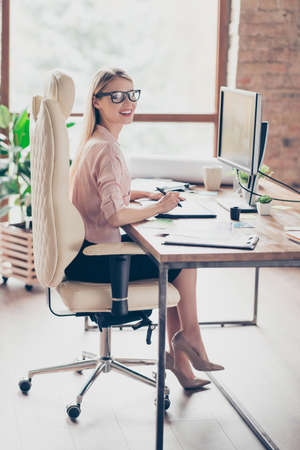 Full length of charming, pretty elegant woman holding tablet pen, businesswoman using digitizer, sitting on armchair at desk in work station, making, drawing sketch, looking at camera