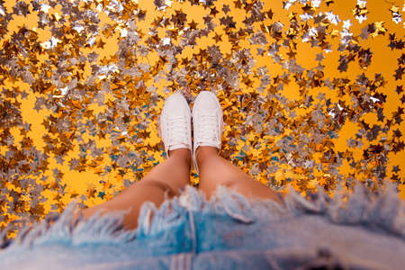 Cropped close up photo of clean white fashionable modern comfortable everyday sportive womans sneakers, legs are standing on yellow floor covered with shiny sparkling stars