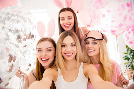 Self portrait of pretty, attractive, charming, cheerful, funny, cute girls shooting selfie on front camera enjoying meeting indoor, celebrating event with air balloons, having rabbit ears and eye mask Foto de archivo