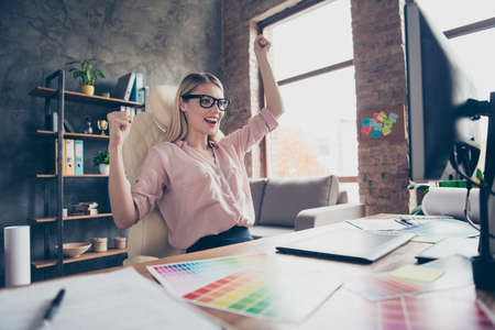 Cheerful, happy, charming, stylish, pretty, attractive woman sitting on chair at desktop in workplace, with raised hands celebrating completed project, looking at monitor Reklamní fotografie