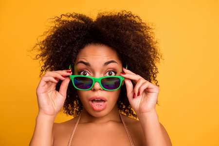 What are you talking about? Cropped close up portrait of surprised funny emotional face expression of beautiful afro with bronze tanned skin fluffy brown hair woman, isolated on yellow background Stockfoto