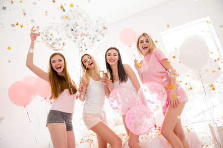 Cheerful slim pretty stylish charming funky girls in night wear in rain of colorful stars, confetti enjoying meeting indoor drinking alcohol laughing standing and looking at camera sleepover party