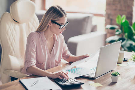 Hardworking, pretty, charming bookkeeper, attractive, stylish financier in shirt counts monthly costs of company, holding report, sitting on armchair at desk in work station