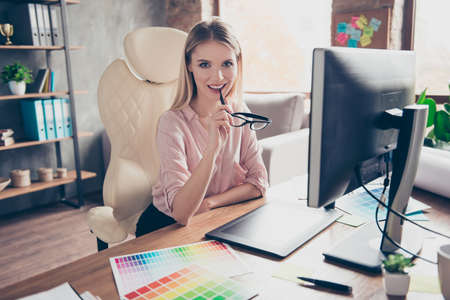 Pretty, charming, dreamy, stylish, modern woman sitting on armchair at her desk, holding glasses in hand, biting eyelet with spectacles, looking at camera