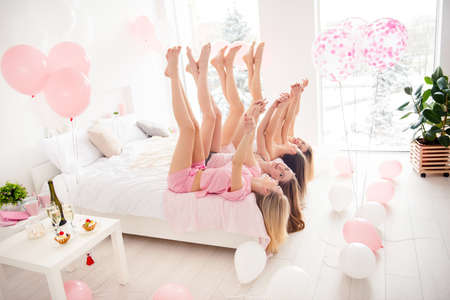 Charming, pretty, cheerful, foolish, attractive, slim, slender girls lying head over heels on bed with crossed legs up, holding hands, celebrating birthday, holiday, event, looking at each other