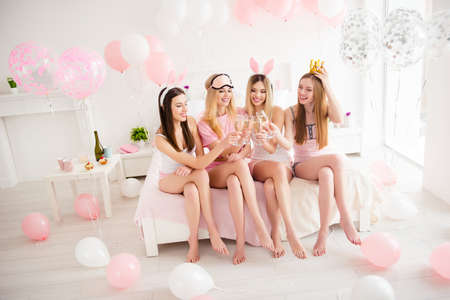 Sexy, charming, pretty, attractive, stylish, cute, cheerful, blonde, brunette girls sitting on bed leg by foot, drinking alcohol, enjoying meeting indoor, having slumber party