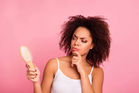 Attractive, pretty, charming, thoughtful, unhappy, sad girl looking at comb in hand touching chin with finger, having dry, oiled hair loss, she need mask, lotion, balm, isolated on pink background Фото со стока