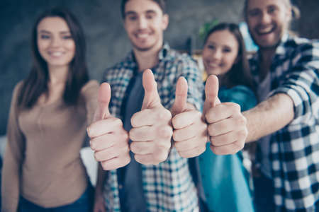 Close up portrait of four thumbs up from cheerful, joyful friends, two couples, colleagues on the blurred background in office, work place, station
