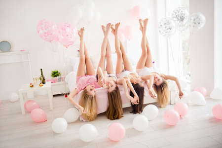 Charming, pretty, cheerful, foolish, attractive, sexy, slender girls lying head over heels on bed with raised crossed legs, holding hands, celebrating birthday, holiday, event, looking at each other