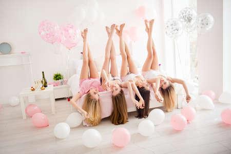 Chicas encantadoras, bonitas, alegres, tontas, atractivas, sexys y delgadas que yacen de cabeza en la cama con las piernas cruzadas levantadas, tomados de la mano, celebrando cumpleaños, vacaciones, eventos, mirándose