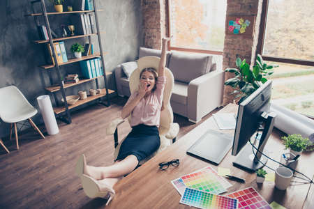 Pretty, attractive, drowsy, somnolent woman putting legs on desk, stretch herself, holding hand near mouth, stand up early for work, sitting on armchair in work station Banque d'images
