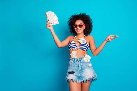 I bathe in money! Funny beautiful wealthy attractive african woman wearing pink glasses striped bra jeans skirt is playing with cash, isolated on blue background
