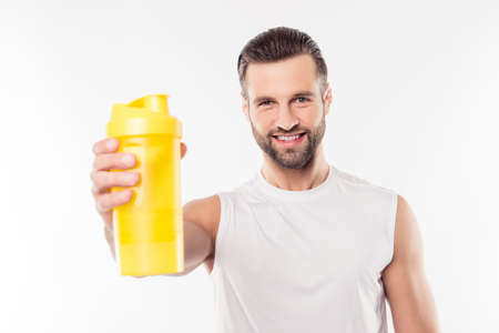 Bodybuilding Supplements - protein, gainer, creatine, bcaa and shaker. Sportive, manly, attractive man in t-shirt having, showing yellow bottle in his hand to the camera, isolated on white background
