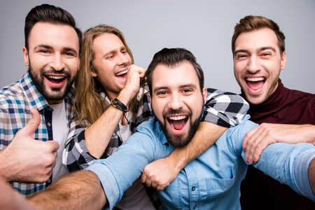 Entertainment holidays leisure lifestyle nightlife concept. Close up photo of four excited cheerful crazy mad handsome guys making selfie casual checkered jeans denim shirt isolated on gray background