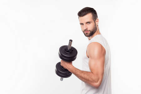 Successful, harsh, virile, attractive, sporty, athletic, professional person lifting weights with hand, arm, having relief biceps, looking at camera isolated on white background 版權商用圖片