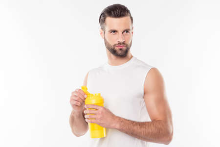 Attractive, virile, harsh, sportive man in white t-shirt holding yellow shaker in hands with creatine for mass, ready for intensive training, looking to the side, isolated on white background Stock Photo