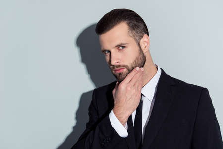 Portrait of thoughtful, virile, harsh, manly, stunning guy in classic outfit touching his beard, suspects something, holding hand on chin, isolated on grey background