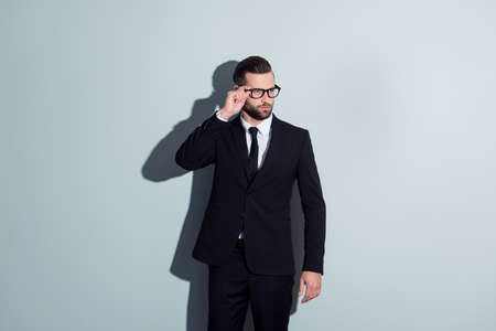 Portrait of perfect, manly, thoughtful, virile, clever, confident, attractive man in formal wear, black pants and jacket, holding eyelet of glasses on his face, looking to the side over grey background Stock Photo