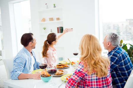Brunette women shooting photo on smart phone with her relatives, guests, visitors in house, apartment, room, festive couples sitting at the table, eating food, drinking wine, domestic lifestyle 版權商用圖片