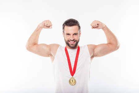 Lucky, attractive, powerful, sporty, athletic man having gold medal with red ribbon on his neck, in t-shirt, hold raised arms, showing relief muscles on his hands, isolated on white background