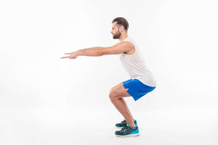 Full length, side view portrait of active, sporty, attractive person showing how it is right to make squats with straight hands, arms forward, isolated on white background Stock Photo