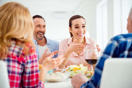 Stylish, cheerful, attractive couple having dinner with relatives, boyfriend hugging, embracing his girlfriend, sitting in house, apartment, room, girl telling to her father gesturing with hand