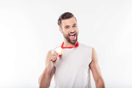 It is mine! Lucky, attractive, powerful, sporty, athletic, strong, cheerful, positive man having gold medal with red ribbon on his neck, showing trophy with hand, yelling over white background 写真素材