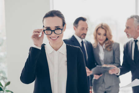 Portrait of modern, positive, nice, smiling, brunet director in formal wear holding eyelet with fingers looking out glasses on her face, her colleagues discuss project, standing on work place, station Stock Photo